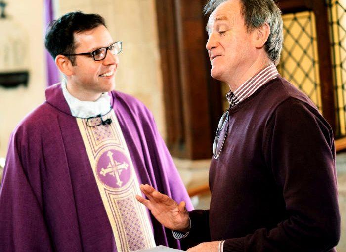 Vicar and parish member in conversation